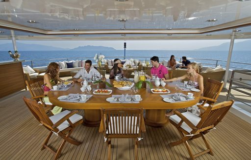 Geusts enjoying food onboard O'MEGA superyacht viewed from top at wooden table on deck under cover