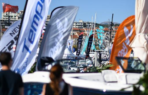 visitors on the boardwalk decorated with shipyard flags at the Cannes Yachting Festival