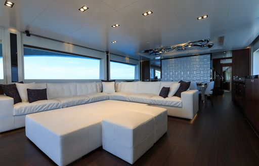 White L-shaped sofa in main salon of charter yacht Paradise