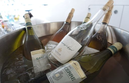 bottles of white and rose wine in an ice bucket on board a superyacht hosting guests for the Monaco Grand Prix