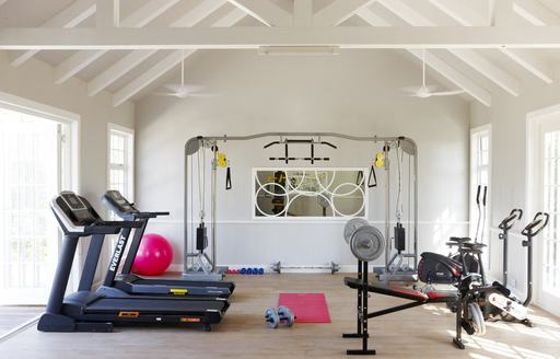gym in villa of thanda island, with treadmills and other gym equipment