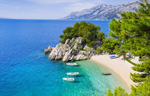 white sandy beach in croatia with green trees in background