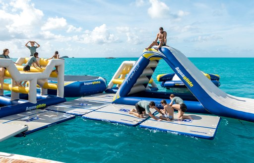 Charter guest playing on inflatable toys aboard megayacht