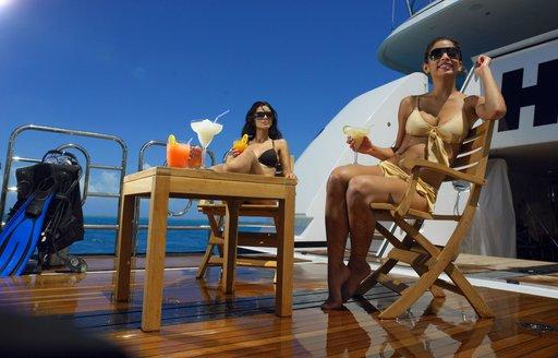 Woman enjoying drinks on beach club of superyacht HARLE in the Caribbean