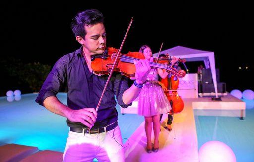 violin players provide entertainment at Kata Rocks Superyacht Rendezvous