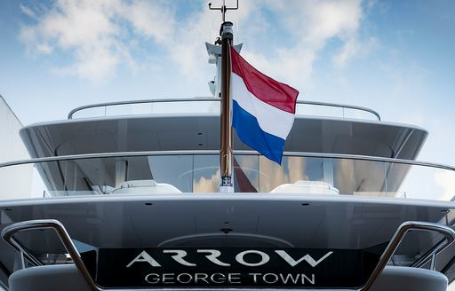 the ensign of charter yacht arrow with the french flag as it cruises the Mediterranean waters