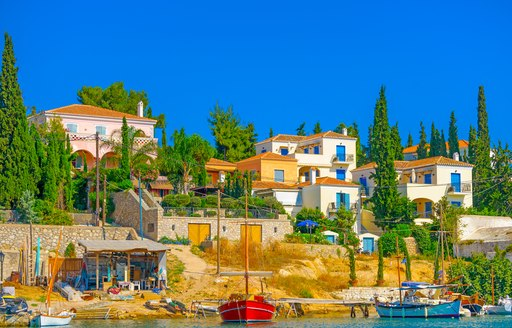 pine trees and fishing boats in front of blue and white houses on the land in greece