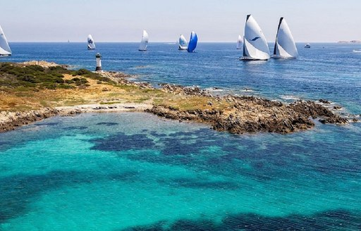 Secluded cove in the Costa Smeralda in Sardinia, with sailing yachts in background