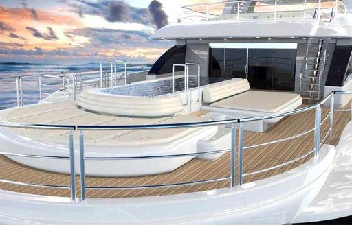 A large swimming pool surrounded by sunpads on the upper deck of a superyacht