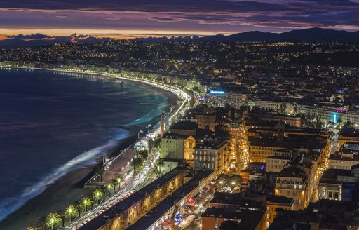 Aerial shot of the glittering city of Cannes at night, with the ocean clearly visible and bright lights throughout the town