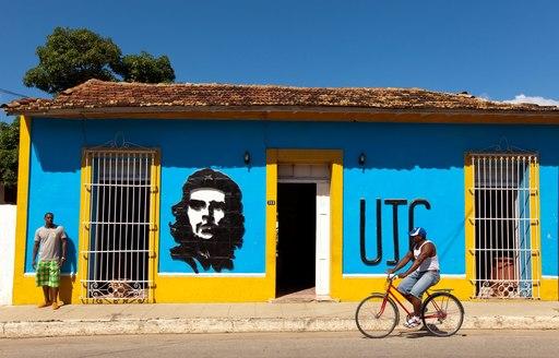 cyclist rides along street in Cuban coastal town