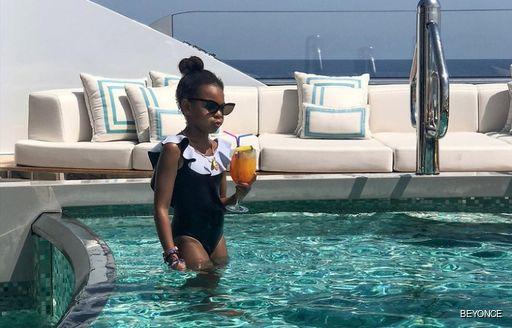Blue Ivy in pool with mocktail aboard superyahct KISMET