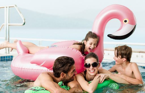 Family laughing and playing in spa pool on board motor yacht TITANIA