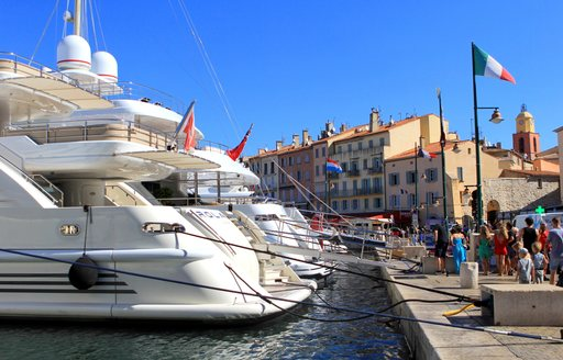 Tourists in the old port of St Tropez, admiring the expensive luxury yachts