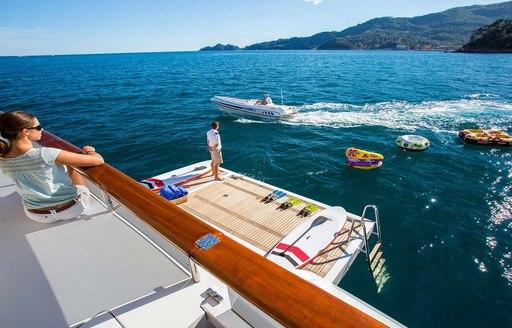 Woman looks over swim platform on luxury yacht DIANE