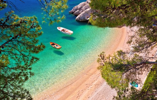 Hiden beach in Brela with boats on emerald sea aerial view, Makarska riviera of Dalmatia, Croatia