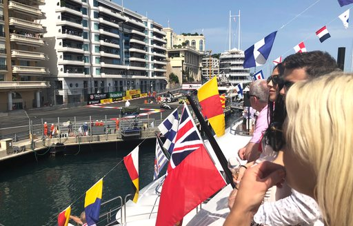 spectators watch the Monaco Grand Prix from the deck of a superyacht
