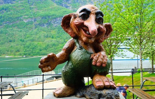 large statue of troll in norway by the water