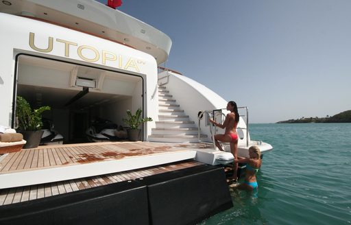 Swim platform and beach club on megayacht UTOPIA, with charter guests climbing on board from stairwell