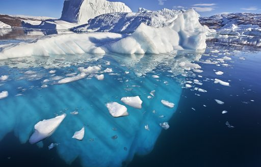 Glacier in fjord in Greenland, icebergs dotted around