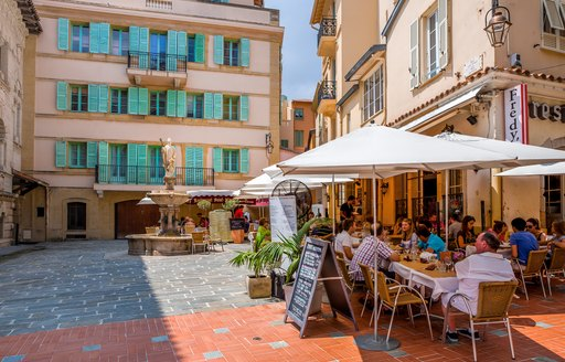 People sat outside around tables in Monaco square