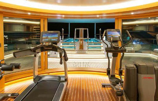 Gym equipment and blue pool on luxury yacht SOLANDGE