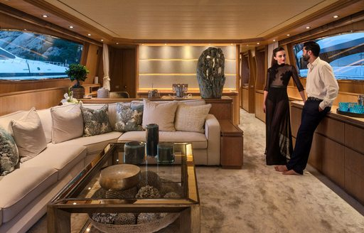 Charter guests relax in main salon of luxury yacht AMAYA