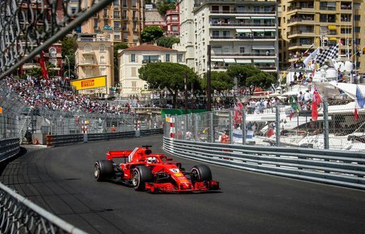 Car on the track at the Monaco Grand Prix with superyachts in background