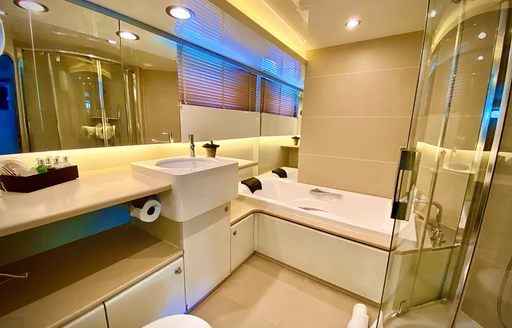 Ensuite with bath and sink in view on superyacht LIONSHARE
