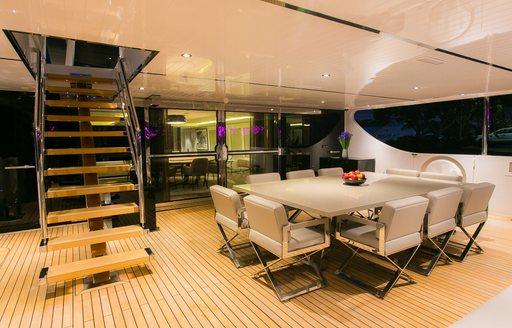 alfresco dining table on the main deck aft of charter yacht SAHANA
