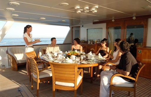 Guest at outdoor table on Top view of Illusion I yacht