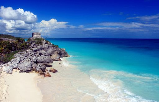 Mexican coast, with white sand beach, azure ocean and Mayan ruins on cliff
