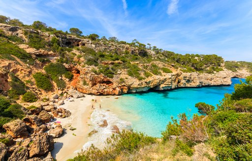 View of beach on Majorca, with rocky coastline behind and clear water at fringe of beach