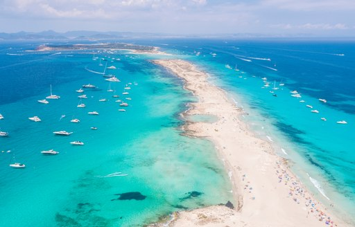 aerial shot of ses illetes beach in fomentera, blue sea and sandy beach