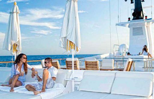 Couple on white sun deck of Illusion I yacht
