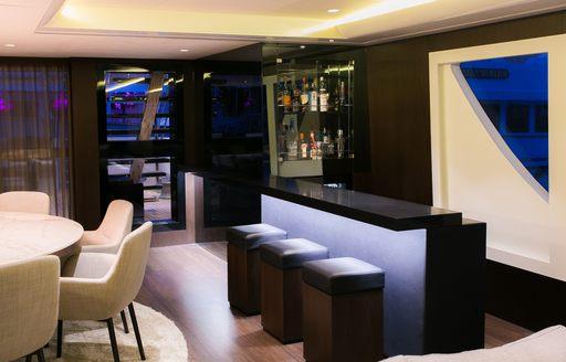 bar next to dining table in the main salon of superyacht SAHANA