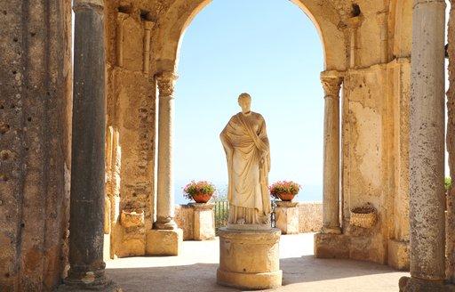 statue in gardens of ravello below archway