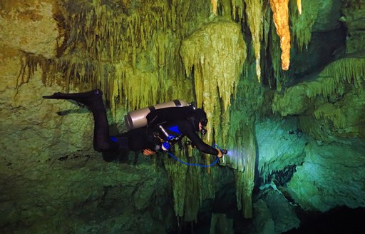Diver swims below stalactites in blue hole