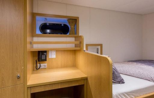 View of bedroom in Game Changer yacht, bed and wooden desk visible