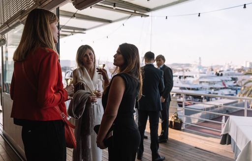 attendees at The Superyacht Show in OneOcean Port Vell, Barcelona, socialise