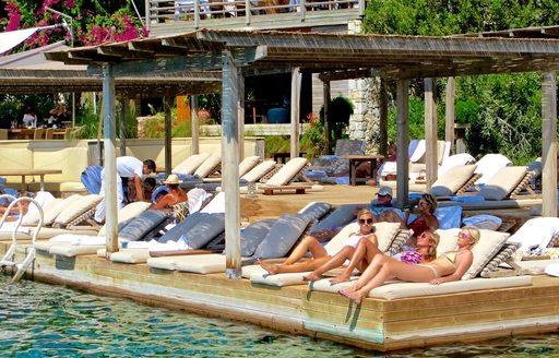 females sunbathe close to the ocean at Maçakizi beach club in Bodrum, Turkey