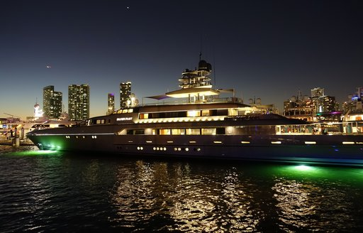 nighttime at miami yacht show, superyachts miami with skyline lit up in background