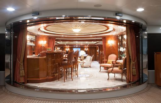 motor yacht st david dining area with polished wood and cream carpet, circular shaped