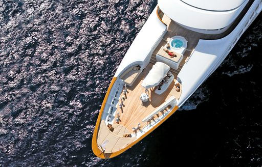 charter guest relaxes on sun pad on the foredeck of luxury yacht Utopia
