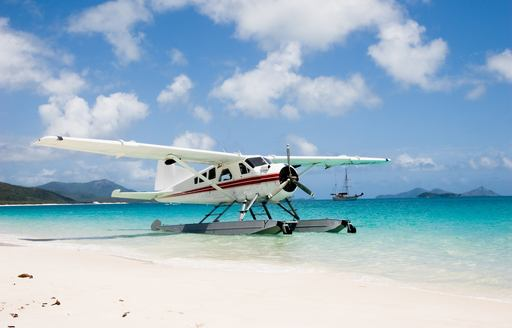 a seaplane lands on the dazzling white sands of a beach in the Whitsundays