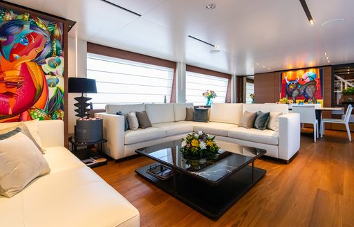 Main salon onboard Ferretti yacht charter 30m PENELOPE, white corner sofa around a black coffee table, coloured paintings on surrounding walls