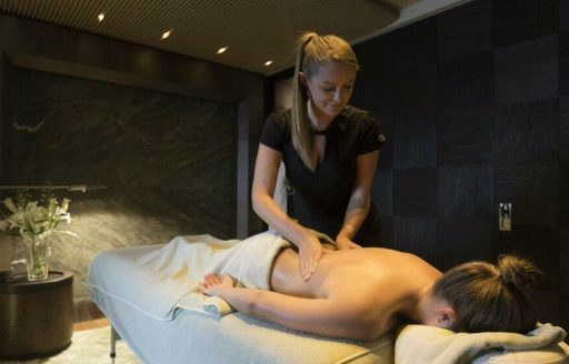 Female charter guest having treatment in massage room onboard luxury yacht charter NIRVANA.