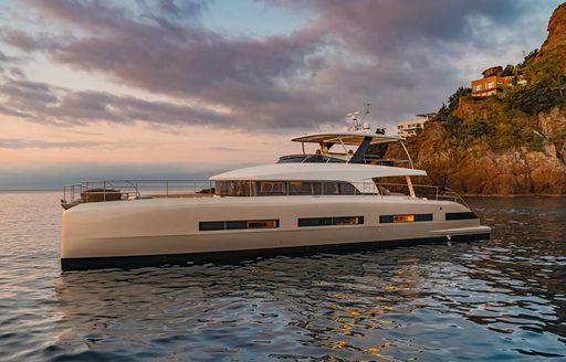 Luxury yacht Double Down profile shot against setting sun
