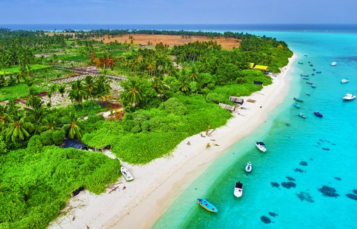 Coastline of a Maldivian island. Lush green foliage bordered by white sands overlooks anchored tenders and clear waters.