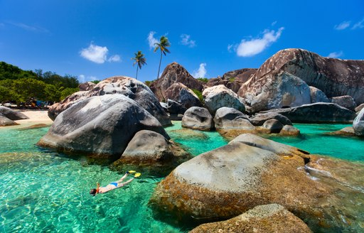 Snorkelling in bright blue sea between famous boulders in the Virgin Islands